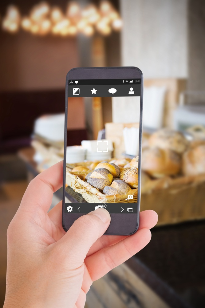 Female hand holding a smartphone against basket with fresh and delicious roll of bread