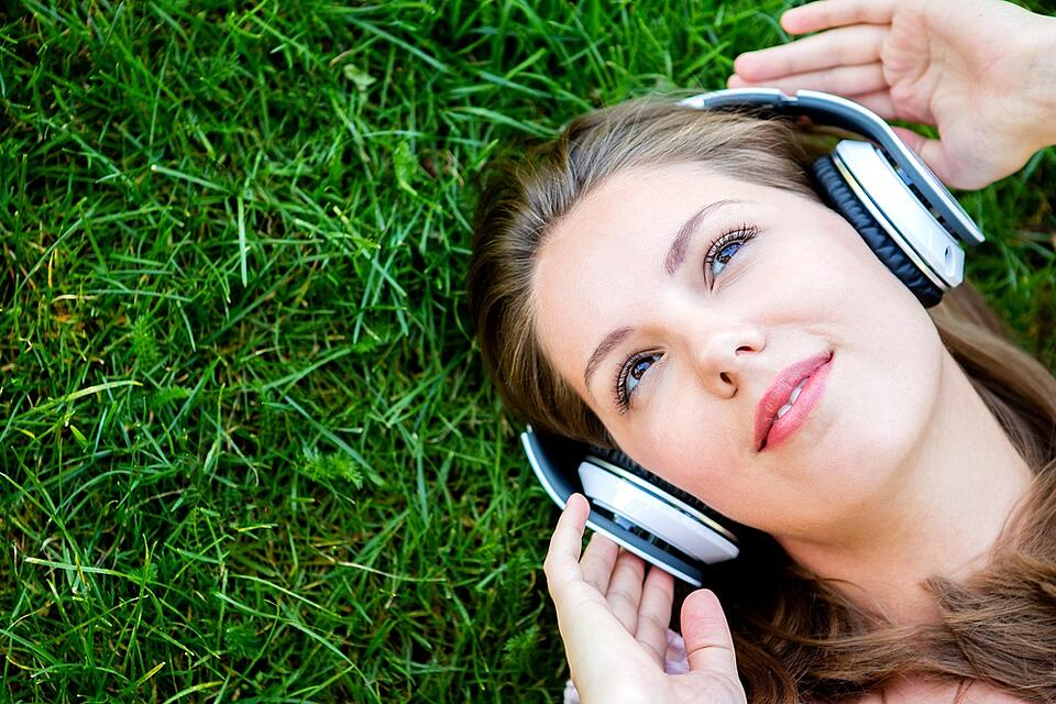 Woman listening to music with headphones at the park-1